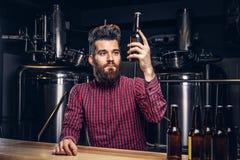 Hippie-Mann mit dem stilvollen trinkenden Bier des Bartes und des Haares, das am Barzähler in der indie Brauerei sitzt stockfoto