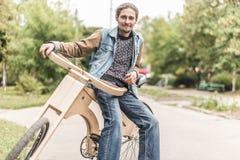 Hippie-Mann mit seinem hölzernen handgemachten Fahrrad des Kreuzers Stockbilder