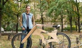 Hippie-Mann mit seinem hölzernen handgemachten Fahrrad des Kreuzers Lizenzfreie Stockfotos