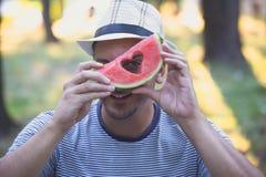Hippie-Manngriff ein Stück Wassermelone und Blicke durch ein Zeichen Lizenzfreie Stockbilder