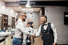 Hippie-Mannkunde, der Hände mit haidresser und Herrenfriseur im Friseursalon rüttelt stockfotografie
