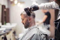 Hippie-Mannkundenbesuchs-haidresser und -Herrenfriseur im Friseursalon, ein Rohr rauchend stockbild
