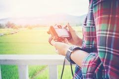 Hippie-Mannphotographie unter Verwendung der Retro- Kamera mit Natur auf dem b Stockfotografie