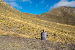 Hippie-Mannreisender an gelbem Hügel Lindis-Durchlauf, Neuseeland Stockfotos