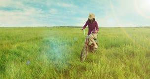 Hippie-Mädchen, das auf grüne Wiese im Sommer radfährt Stockbild
