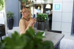 Hippie-Mädchen, das am intelligenten Telefon in der Bürgersteigskaffeestubeterrasse plaudert Stockbild