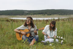 Hippie men play on the guitar and woman make a wreath Royalty Free Stock Photo