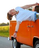 Happy young man in a van on a road trip Royalty Free Stock Image
