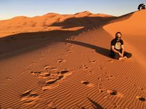 Hippie Men sitting in the Sahara Desert, somewhere in Morocco stock photo