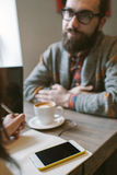 Hippie mit Bart mit Smartphone und Laptop auf der Tabelle, die nachgibt Lizenzfreie Stockbilder