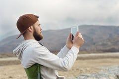Hippie mit einem Bart in einer Kappe und einem Sweatshirt mit einer Tablette in seinen Händen macht Fotos auf einer Tablette beim Stockfotos