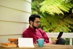Hippie mit einem Leser, der draußen sitzt stockfotografie