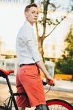 Hippie mit rotem bycicle und Tätowierung auf Bein Stockfotos