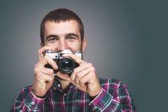 Hippie-Modefotografmann, der Retro- Kamera hält Stockbild