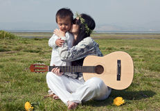 Hippie mother kisses son on cheek. A young hippie mother kisses her son on the cheek while holding a guitar in the park royalty free stock photos