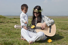 Hippie mother playing guitar with son. A young hippie mother plays the guitar while her son holds a yellow flower over the strings Stock Image
