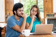 Hippie-Paare, die an on-line-Angebot am Computer denken stockbild