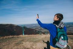 Hippie prenant la photo par le Smart-téléphone sur la crête du mountai Photographie stock