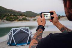 Hippie-Reisemann macht Foto vom Zelt lizenzfreies stockfoto