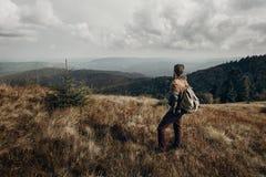 Hippie-Reisender mit dem Rucksack, der auf Berge aufwirft wande stockbilder