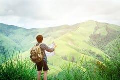 Hippie-Reisendmann, der Karte an den Bergen mit erstaunlicher Ansicht hält Stockbild
