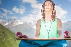 Hippie relajante y hombre hermoso que escucha la música con el monopatín Foto de archivo