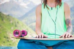 Hippie relajante y hombre hermoso que escucha la música con el monopatín Imagenes de archivo