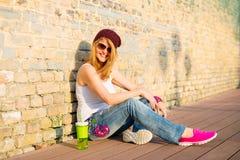 Hippie s'asseyant au sol en verres de chapeau et de soleil Image stock