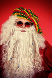 Hippie Santa. Portrait of a casual Santa Claus hippie over festive red background royalty free stock photography