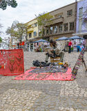 Hippie selling his art on Londrina downtown. Londrina, Brazil - July 31, 2017: Hippie selling his art on Londrina downtown, jewelry on the floor, handcrafted Stock Image