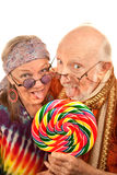 Hippie seniors licking a lollipop royalty free stock photo