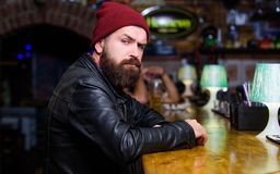 Hippie seul brutal L'homme barbu de hippie brutal s'asseyent au compteur de barre Vendredi soir Hippie d?tendant ? la barre La ba images libres de droits