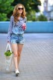 Hippie sexy de femme avec la nourriture et la boisson saines dans leurs mains sur une rue de ville Image libre de droits