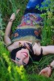 Hippie sonriente de la muchacha que miente en la hierba y las flores Estilo de Boho, Foto de archivo libre de regalías