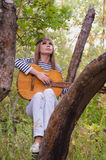 Hippie-style girl posing with a guitar Stock Photo