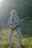 Hippie-style girl posing with a guitar Royalty Free Stock Images