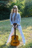 Hippie-style girl posing with a guitar Stock Image