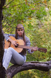 Hippie-style girl posing with a guitar on a tree Royalty Free Stock Images