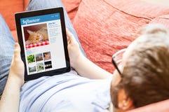 Hippie sur le sofa avec le comprimé de vente d'influencer Photographie stock libre de droits