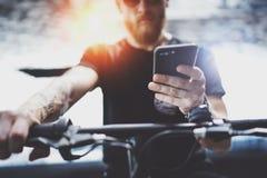 Hippie tatoué musculaire barbu dans des lunettes de soleil utilisant le smartphone après la monte en le scooter électrique dans l image libre de droits