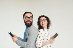 Hippie-Team in den Gläsern mit der Smartphonetablette lokalisiert auf Weiß Lizenzfreie Stockbilder