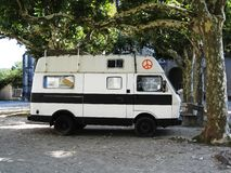 Hippie van. A white hippie van with a red hippie sign parked in a shade under a wood crown in French at Montelimar royalty free stock photo