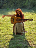 Hippie woman. A handsome smiling brunette woman with a flowers in his hair sitting on the green grass playing guitar and singing a song. Vertical color photo royalty free stock photography