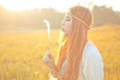Hippie woman blowing flower Stock Images