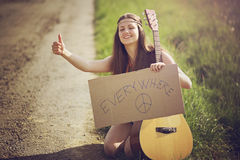 Hippie woman on a country road hitch-hiking Royalty Free Stock Photo