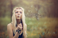 Hippie woman. With crown of flowers blowing flower dandelion Stock Photo