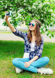 Hippie woman makes self-portrait on smartphone sitting on grass in flowering garden. Beautiful hippie woman makes self-portrait on smartphone sitting on grass in Royalty Free Stock Images