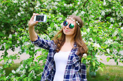 Hippie woman makes self portrait on smartphone in spring flowering garden. Beautiful hippie woman makes self portrait on smartphone in spring flowering garden Stock Photo