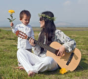 Hippie Woman playing Guitar with Son. A hippie woman plays the guitar as her son looks on holding a yellow flower royalty free stock image