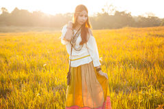 Hippie woman posing in golden field. On sunset Stock Photography
